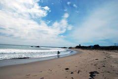 Il surfista cammina lungo la spiaggia fotografia stock libera da diritti