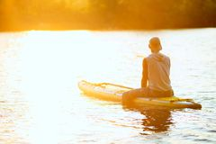 Il surfista del Sup si siede sul bordo del sup alla luce dorata fotografia stock libera da diritti