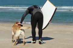 Il surfista ed è cane Fotografia Stock Libera da Diritti