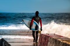 Il surfista entra in acqua nell'inverno Immagini Stock