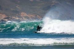 Il surfista guida una buona alta onda verso la riva Immagini Stock Libere da Diritti