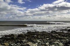 Il surfista pratica il surfing un'onda perfetta un giorno soleggiato Fotografie Stock Libere da Diritti