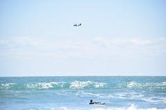 Il surfista rema fuori mentre l'aeroplano sorvola l'orizzonte immagini stock libere da diritti