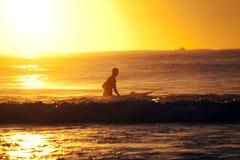 Il surfista si siede sul surf all'alba Immagini Stock