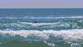 Il surfista si trova a bordo delle pagaie in onde contro la barca video d archivio