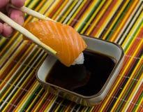 Il sushi di color salmone è tenuto con i bastoncini nei precedenti di una ciotola fotografia stock