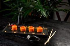 Il sushi rotola l'insieme con il tonno su una banda nera su un fondo di legno nero fotografia stock