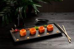 Il sushi rotola l'insieme con il tonno su una banda nera su un fondo di legno nero fotografie stock libere da diritti