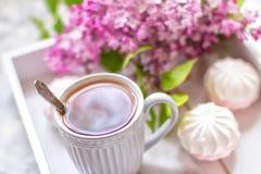 Il tè è servito in un contenitore di regalo con le caramelle gommosa e molle ed in un mazzo di un lillà Fine in su fotografia stock