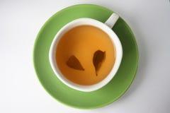 Il tè è in una tazza, con due foglie di tè sopra fotografia stock libera da diritti
