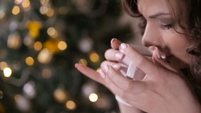 Il tè bevente della bella ragazza vicino ha decorato l'albero di Natale, sedentesi in una sedia comoda e accogliente video d archivio