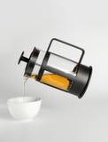 Il tè che versa dal francese introduce una tazza bianca Immagini Stock