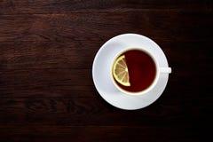 Il tè con il limone in tazza bianca, bastoni di cannella, ha tricottato la sciarpa di lana sulla tavola di legno Immagini Stock Libere da Diritti