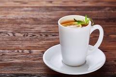 Il tè con il limone in tazza bianca, bastoni di cannella, ha tricottato la sciarpa di lana sulla tavola di legno Fotografia Stock