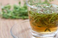 Il tè del timo con timo fresco lascia il tazza da the interno Fotografia Stock