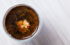 Il tè di fioritura ed asciuga i fiori su fondo di legno Immagini Stock Libere da Diritti