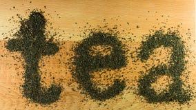Il tè di parola è presentato su un tè nero foglia marrone chiaro del bordo di legno della piccola Immagini Stock