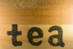 Il tè di parola è presentato su un tè nero foglia marrone chiaro del bordo di legno della piccola Immagine Stock Libera da Diritti