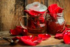 Il tè fatto dai petali rosa del tè in una ciotola di vetro su fondo rustico di legno ha tonificato l'immagine Fotografia Stock