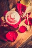 Il tè fatto dai petali rosa del tè in una ciotola di vetro su fondo rustico di legno ha tonificato l'immagine Fotografia Stock Libera da Diritti