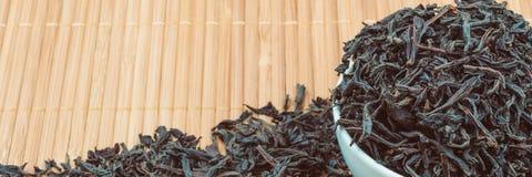 Il tè secco è versato in una tazza ceramica su una stuoia di bambù fotografia stock libera da diritti