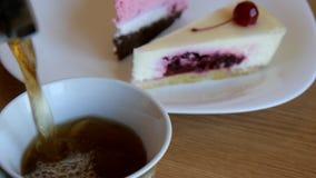 Il tè sta versando nella tazza sul dolce del mirtillo rosso del fondo e sulla torta di formaggio della ciliegia stock footage