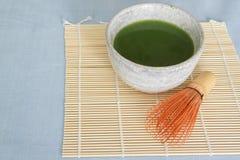 Il tè verde di Matcha in ciotola bevente di pietra su placemat di bambù con di legno sbatte Fotografia Stock
