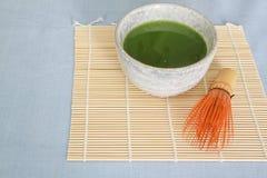 Il tè verde di Matcha in ciotola bevente di pietra su placemat di bambù con di legno sbatte Immagine Stock