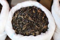 Il tè verde ha asciugato i fogli su un servizio in Cina immagini stock