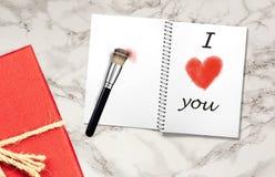 Il taccuino aperto sulla vecchia tavola di legno d'annata con ti amo forma scritta a mano e rossa del cuore ha dipinto con il pen immagini stock libere da diritti