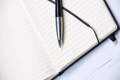 Il taccuino bianco del blocco note allinea il fondo di legno della penna elegante Immagini Stock Libere da Diritti