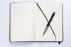 Il taccuino bianco del blocco note allinea il fondo di legno della penna elegante Immagine Stock