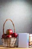 Il taccuino con una matita e le mele sono sulla tavola Immagine Stock