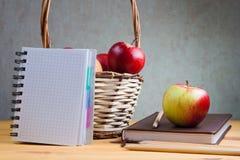 Il taccuino con una matita e le mele sono sulla tavola Immagini Stock