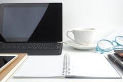 Il taccuino della pagina in bianco sul desktop bianco con la penna, caffè, computer portatile fotografia stock libera da diritti
