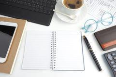 Il taccuino della pagina in bianco sul desktop bianco con la penna, caffè, lapto fotografie stock libere da diritti