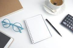 Il taccuino della pagina in bianco sul desktop bianco con la penna, caffè, lapto fotografia stock