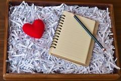 Il taccuino e la matita in bianco hanno messo la carta sopra tagliuzzata con cuore rosso i Immagini Stock