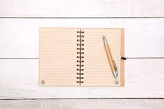 Il taccuino ha riciclato lo spazio in bianco di carta sulla tavola di legno con la penna Immagini Stock