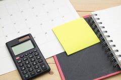 Il taccuino, il calcolatore, il Post-it ed il calendario di vista superiore hanno messo sopra w Fotografie Stock Libere da Diritti