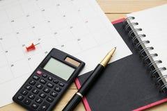 Il taccuino, il calcolatore, la penna ed il calendario di vista superiore hanno messo sopra il flo di legno Immagini Stock Libere da Diritti
