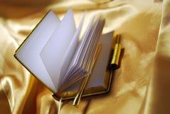 Il taccuino personale aperto organizza su oro Fotografia Stock