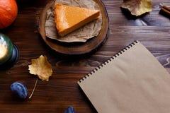 Il taccuino, torta di formaggio della zucca, ha cucinato a casa, zucca, fogliame, lampada da tavolo, vaniglia su uno spazio scuro immagini stock libere da diritti