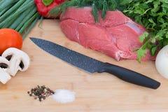 Il tagliere con il pomodoro, il prezzemolo ed il raccordo crudo del manzo ha attaccato con il coltello Fotografie Stock