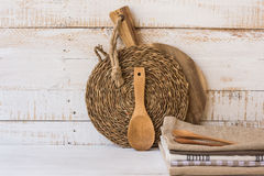 Il tagliere di legno, il sottobicchiere del rattan, il cucchiaio, pila di asciugamani di tela sulla tavola di legno, modello, ha  Fotografia Stock Libera da Diritti