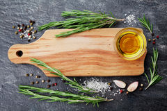 Il tagliere di legno, l'olio d'oliva, rosmarino pianta, sala, aglio e pepe sulla tavola nera da sopra per alimento cucinante il f fotografie stock libere da diritti