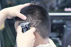 Il taglio di capelli del ragazzo con il tagliatore ed il rasoio nel negozio di barbiere Fotografie Stock