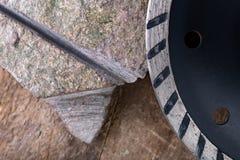 Il taglio di pietra con un disco del diamante ha montato in una smerigliatrice Lavoro in un'officina di pietra immagine stock