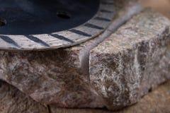 Il taglio di pietra con un disco del diamante ha montato in una smerigliatrice Lavoro in un'officina di pietra fotografia stock