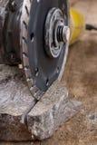 Il taglio di pietra con un disco del diamante ha montato in una smerigliatrice Lavoro in un'officina di pietra immagini stock